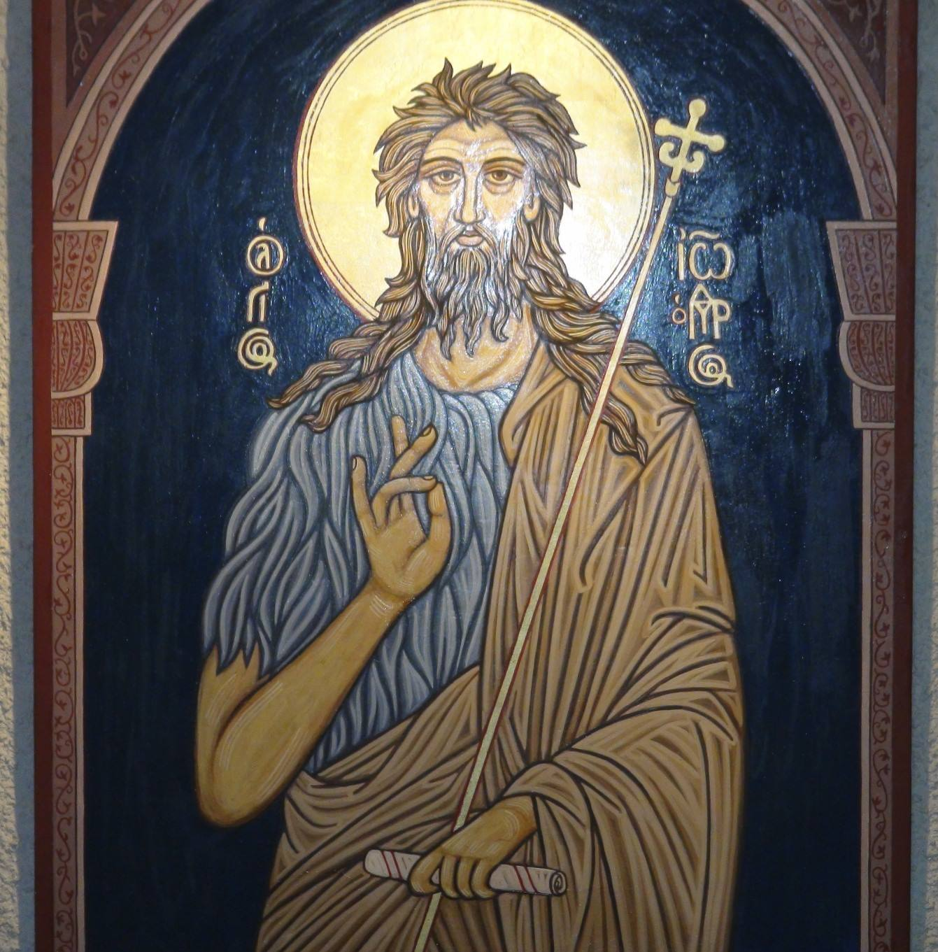 an ancient icon of John the Baptizer, showing his hairy shirt and staff with a Russian style cross on the top.